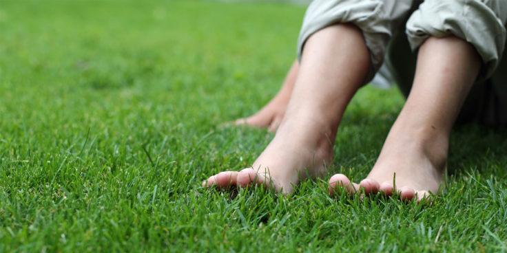 nainen istuu vihreällä nurmikolla
